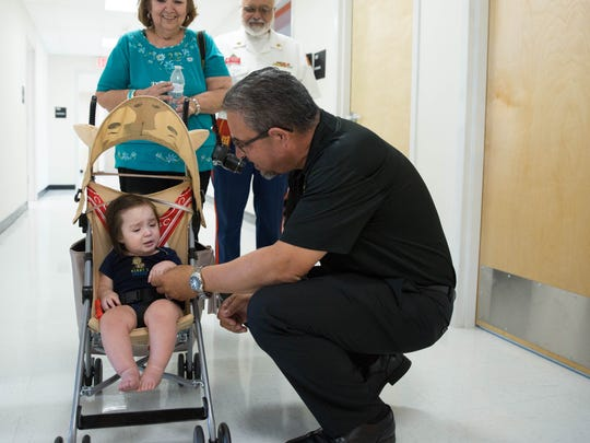 La Clinica de Familia's new interim CEO Virgil Medina,right, talks to eight-month old, Cruz Jaquez, as Jaquez and his grand parents Joe and Doreen Meddiola tour the   new Cervantes Complex  Central Medical Center, Friday May 5, 2017.