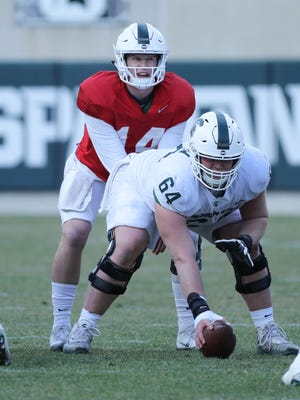 Michigan State quarterback Brian Lewerke takes the snap from center Matt Allen during the spring game Saturday, April 7, 2018 at Spartan Stadium.