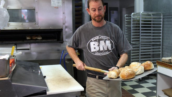 Darren Weinstein, owner of Bagel Masters, takes fresh bagels out of the oven in his restaurant in Shewsbury.