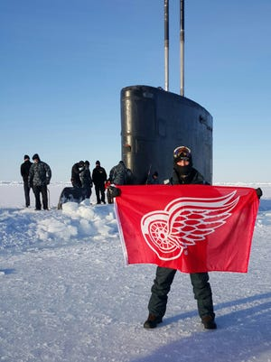 Petty Officer Second Class Benjamin Osberger, ETR2, is aboard the USS Hartford, SSN 768,  a Los Angeles-class Fast Attack Submarine. Benjamin managed to take Red Wings flag and then bring it out in the brisk -30 Arctic weather when the sub broke through the ice north of the Arctic Circle. He grew up in Rochester Hills and is stationed in Groton, Conn. The picture was taken by Petty Officer Second Class Hector Maldonado, LS2, USS Hartford, of Benjamin Osberger on March 31, 2016 about 10 miles south of the North Pole. His submarine surfaced several time through the ice from Arctic Alaska to the geographic North Pole. This picture was taken at the North Pole.