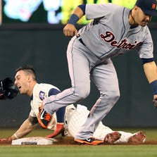 Minnesota Twins' Jordan Schafer, left, loses his helmet as he steals third on Detroit Tigers shortstop Eugenio Suarez in the eighth inning.