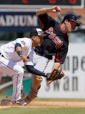 The Atlanta Braves' Joe Benson is caught stealing by Detroit Tigers shortstop Jose Iglesias in Lakeland, Fla., on March 30, 2015.