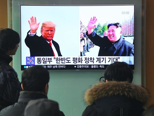 People watch a television news report showing pictures of President Trump, left, and North Korea leader Kim Jong Un at a railway station in Seoul on March 9.