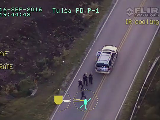 In this image made from a Friday, Sept. 16, 2016 police video, Terence Crutcher, top, is pursued by police officers as he walk to an SUV in Tulsa, Okla. Crutcher was taken to the hospital where he was pronounced dead after he was shot by the officer around 8 p.m., Friday, police said. Crutcher had no weapon on him or in his SUV, Tulsa Police Chief Chuck Jordan said Monday, Sept. 19, 2016.  (Tulsa Police Department via AP)