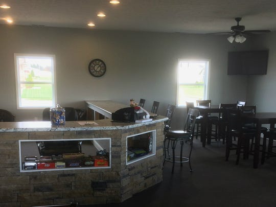 The interior of the new clubhouse at Bent Creek Golf Course includes a brick and granite counter along with tables with seating for several customers.