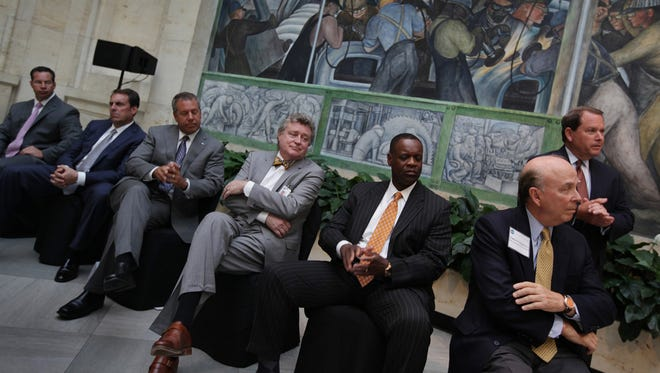 From left, Chrysler executive Reid Bigland, General Motors' Mark Reuss, Ford Motor Co.'s Joe Hinrichs, Detroit Institute of Arts Director Graham Beal, Detroit emergency manager Kevyn Orr, Chief U.S. District Judge Gerald Rosen and Detroit Institute of Arts Chairman of the Board Eugene Gargaro Jr. listen during a news conference announcing pledges to the DIA's grand bargain commitment in June 2014 in the Rivera Court at the Detroit Institute of Arts. Detroit's bankruptcy trial starts Tuesday, Sept. 2, 2014, and the city is facing pressure to prove the grand bargain is fair.