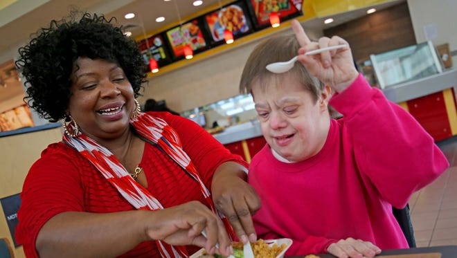 Rosa Dodd (left) helps Gloria Dawson with her lunch at Mayfair mall in Wauwatosa. Dodd has been Gloria's caregiver for 28 years. Gloria has Down syndrome and when her mother died, she refused to come out of her room. Under Dodd's gentle prodding, Gloria slowly emerged back into the world.