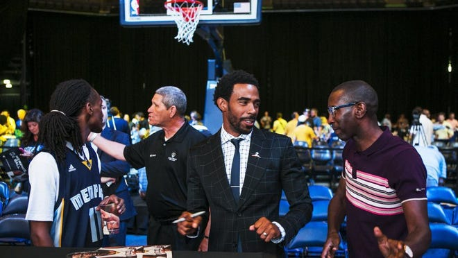 July 14, 2016 — Memphis Grizzlies point guard Mike Conley (center) chats with Elliot Perry (right), Grizzlies Partner & Foundation Board Chair, as he prepares to sign an autograph for fan Jonathan Shavers (left) at FedExForum on Thursday. Conley re-signed with the Grizzlies to a five-year, $153 million contract. He said the deal is 'is a tremendous opportunity. I'm so excited for these next five years.' (Yalonda M. James/The Commercial Appeal)