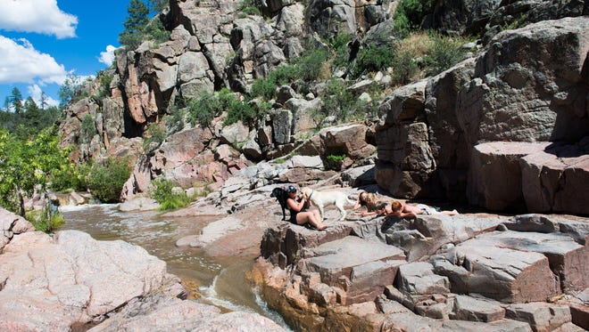 Melissa Brooks, left, sits with her dogs as, left to right, Emily Daniels, 13, Delaney Brooks, 8, Dylan Brooks, 12, and Caden Bowman, 12, lay out on the rocks near some rapids at Water Wheel recreational area on Houston Mesa Road just north of Payson in Tonto National Forest on July 6, 2015.