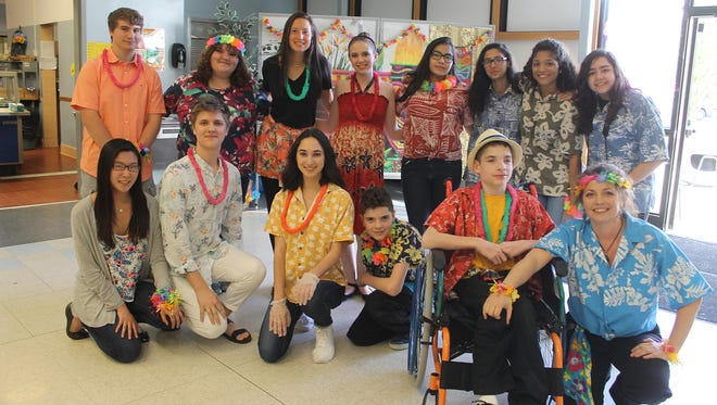 """Highland teacher and Interact adviser AnnMarie Phillips Meisel, front, kneeling, is shown with the Interact students and family members who helped serve the special """"luau dinner"""" during the 12th annual Senior Citizen Prom at Highland High School. Meisel has been helping to coordinate the event for the last five years."""