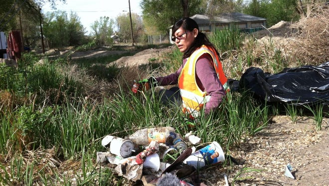 "A frame from ""The Mayors of Shiprock"" shows a member of the Northern Diné Youth Committee participating in the group's Earth Day community cleanup."