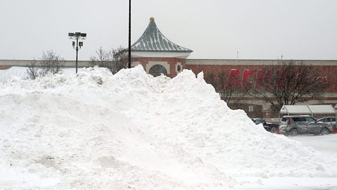 Plow trucks make a mountain of snow in the Acme parking lot on South Main Road in Vineland.
