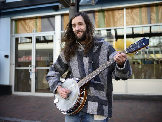 Will Northrop plucks away at his banjo on Church Street