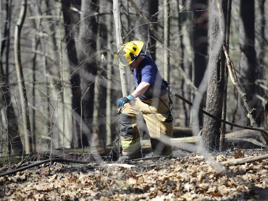 Firefighters work to contain a brush fire in South
