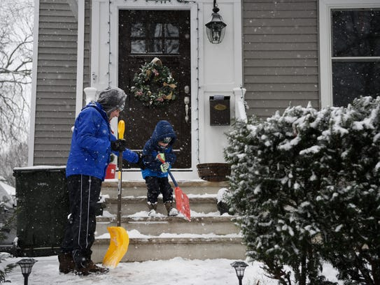 Mike Giacalone and his son Michael, 4, clear snow from