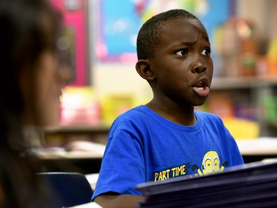 Second-grade student Maku Adriano reacts while reading