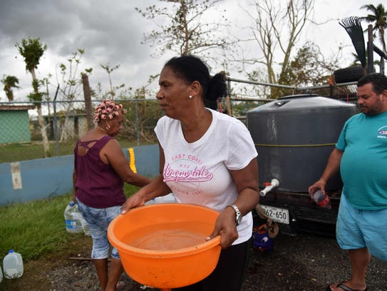 A woman carries water taken from a tank in Vega Baja,