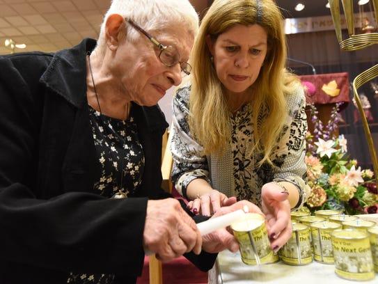 Holocaust survivor Bracha Adler lights up a candle