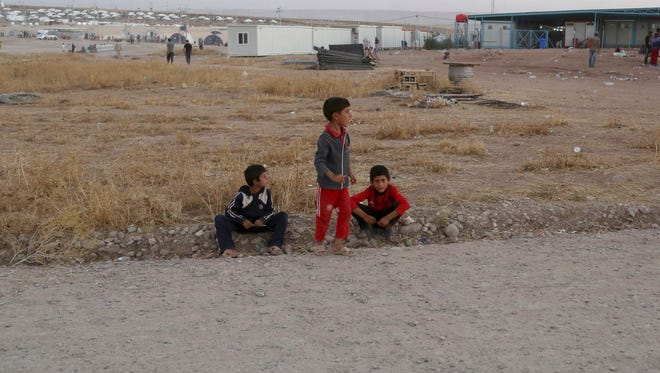 Displaced Iraqi boys from the Yazidi community wait at the entrance of the camp of Bajid Kandala  as they look for their family members who they became separated from during their escape, at Feeshkhabour town near the Syria-Iraq border, in Iraq on Saturday.