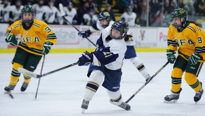 Essex's Madeline Young (21) shoots the puck during the Division I girls hockey championship game between the Essex Hornets and the BFA-St. Albans Comets at Gutterson Fieldhouse on March 12.