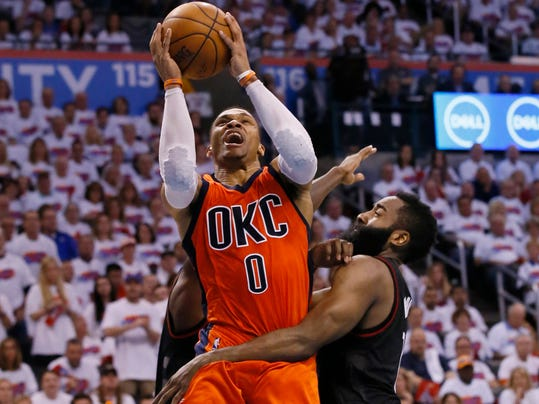 Oklahoma City Thunder guard Russell Westbrook (0) shoots between Houston Rockets guards Patrick Beverley, rear, and James Harden, right, in the fourth quarter of Game 4 of a first-round NBA basketball playoff series in Oklahoma City, Sunday, April 23, 2017. (AP Photo/Sue Ogrocki)