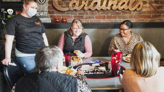 Manager Elyse Quarterman checks in on a group of diners during lunch hour at Charred 51 Artisan Bar & Bistro, 51 N. Prairie St., on Monday.