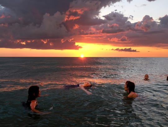 As the sun makes its final descent into the Gulf of Mexico a group of teenage girls play at Vanderbilt Beach Sunday, May 29, 2016, in Naples.