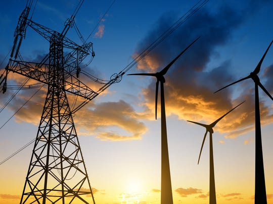 An electrical transmission tower next to three wind turbines at sunrise