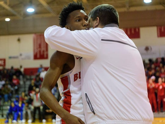 Bosse's Mekhi Lairy (2) receives a hug from Head Coach Shane Burkhart after breaking the school's career scoring record while playing the Memorial Tigers at Bosse High School in Evansville, Ind., Tuesday, Dec. 12, 2017. Lairy's record reached 1,560 points, breaking a 1967 record of 1,559 points set by Larry Weatherford.