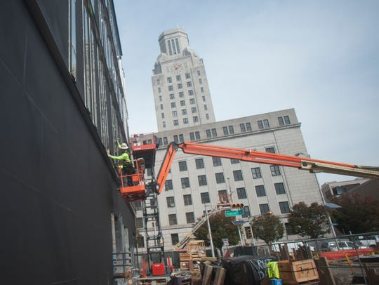 A workers places windows at the new Rutgers-Camden
