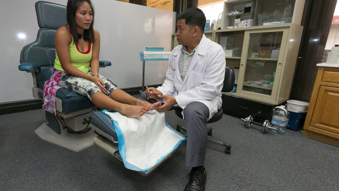 Dr. Noel Silan, right, demonstrates how he would examine a patient at the Guam Foot Clinic in Dededo on Nov. 7.