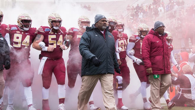 Florida State interim head coach Odell Haggins and the team walk out together at the beginning of the Walk On's Independence Bowl in Shreveport, Louisiana.