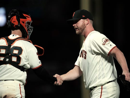 San Francisco Giants pitcher Will Smith, right, celebrates with catcher Buster Posey at the end of the team's baseball game against the Colorado Rockies Thursday, April 11, 2019, in San Francisco. The Giants won 1-0. (AP Photo/Ben Margot)