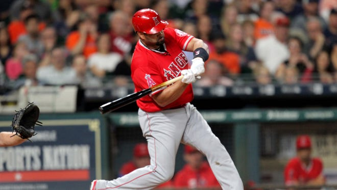 Los Angeles Angels designated hitter Albert Pujols (5) hits a three-run home run to left field against the Houston Astros during the fifth inning at Minute Maid Park.