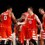 Syracuse guards Michael Gbinije (0) and Trevor Cooney (10) celebrate a play against in last week's win over Connecticut as freshman forward, Tyler Lydon, far right, also gets revved up.