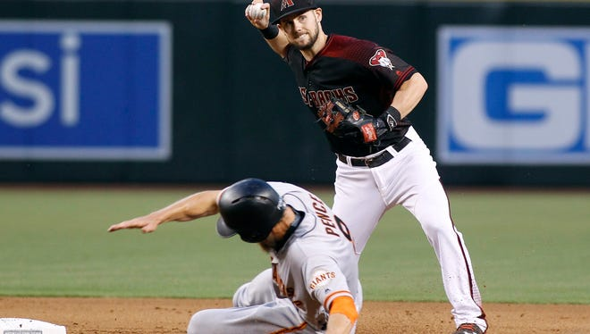 Arizona Diamondbacks shortstop Chris Owings is forced wide to make his throw by the slide of San Francisco Giants' Hunter Pence on a ball hit by Joe Panik during the fifth inning, Saturday, September 10, 2016, in Phoenix.
