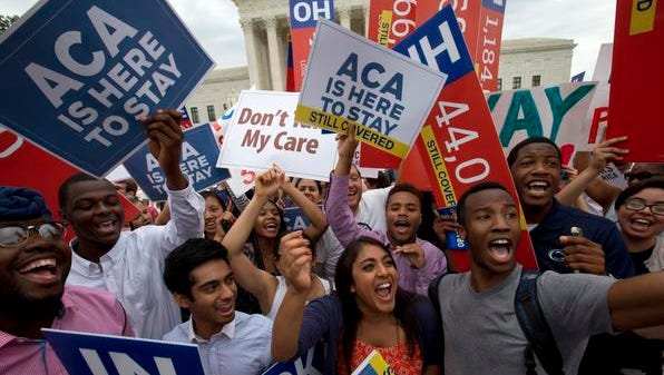 Students cheer as they hold up signs supporting the Affordable Care Act (ACA) after the Supreme Court decided that the ACA may provide nationwide tax subsidies, Thursday June 25, 2015, outside of the Supreme Court in Washington.