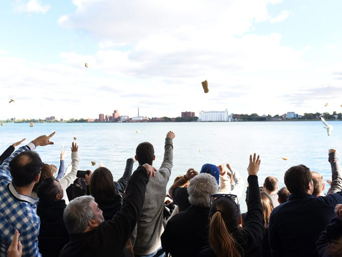 People throw pieces of bread into the Detroit River