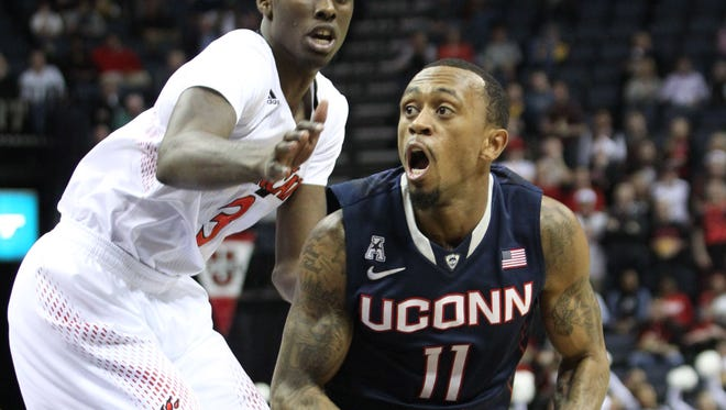 Connecticut Huskies guard Ryan Boatright (11) drives to the basket defended by Cincinnati Bearcats forward Shaquille Thomas (3).