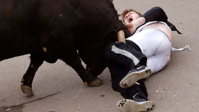 """In this Saturday, Feb. 14 photo, Ole Miss student Benjamin Milley, 20, from Georgia, in the US,  is gored by a bull during the """"Carnaval del Toro"""" in Ciudad Rodrigo, Spain."""