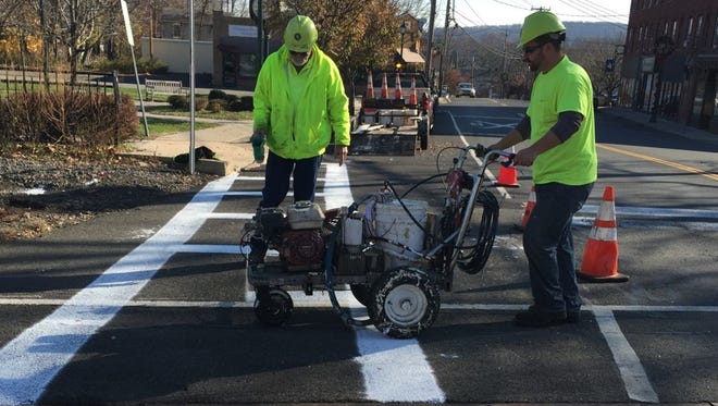 Rockland County highway workers apply a fresh coat of paint that will help illuminate the Lake Road rail crossing, which saw two train-car crashes last week.