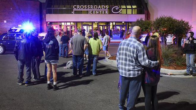 People stand near the entrance on the north side of Crossroads Center mall between Macy's and Target as officials investigate a reported multiple stabbing incident, Saturday, Sept. 17, 2016, in St. Cloud, Minn. Police said multiple people were injured at the St. Cloud shopping mall on Saturday evening in an attack possibly involving both shooting and stabbing. The suspect is believed to be dead, St. Cloud Police Sgt. Jason Burke told the St. Cloud Times.