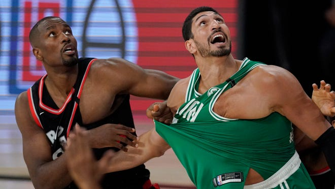 Toronto Raptors' Serge Ibaka, left, grabs the jersey of Boston Celtics' Enes Kanter, right, as they watch the ball in the second half of an NBA conference semifinal playoff basketball game Thursday, Sept 3, 2020, in Lake Buena Vista Fla.