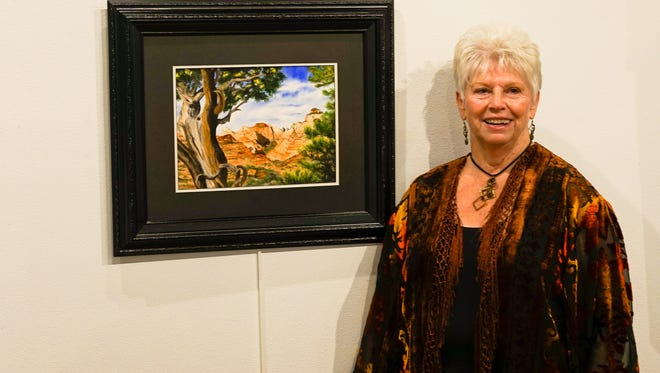 Karlynn Jones stands next to one of her paintings at the Mesquite Fine Arts Gallery.
