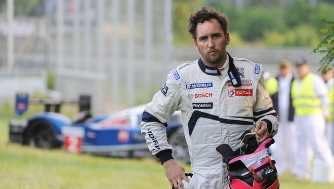 FILE - French pilot Franck Montagny waits for assistance after giving up the Le Mans 24-hour endurance race, on June 13, 2010, due to a start of fire in his car, in Le Mans western France.