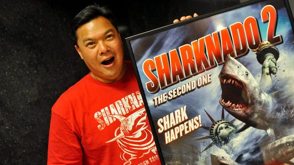 """Lyman Chen, of Brandywine Hundred, jokes around next to a """"Sharknado 2: The Second One"""" movie poster during its screening at Theater N in Wilmington Wednesday."""