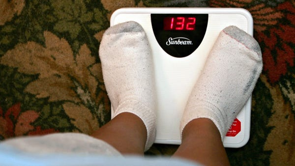 James Hernandez, 10, weighs himself in July 2004 after losing 43 pounds.