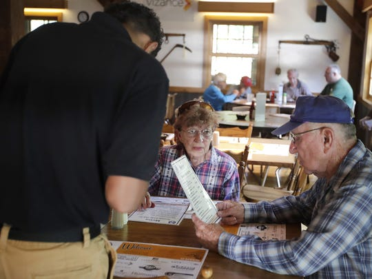 A boy takes an order for Bertrant Behm and his wife, Joann, of Oshkosh, during a recent fish fry at Rawhide Boys Ranch.