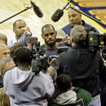 Cleveland Cavaliers' LeBron James, center, is besieged by the media after practice Wednesday.