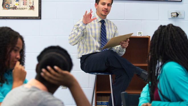 Varsity Lakes Middle School teacher Gregory Balan discusses a few key argument points during his rhetoric class Wednsday (3/25/15). Balan became the first Golden Apple winner ever from school.